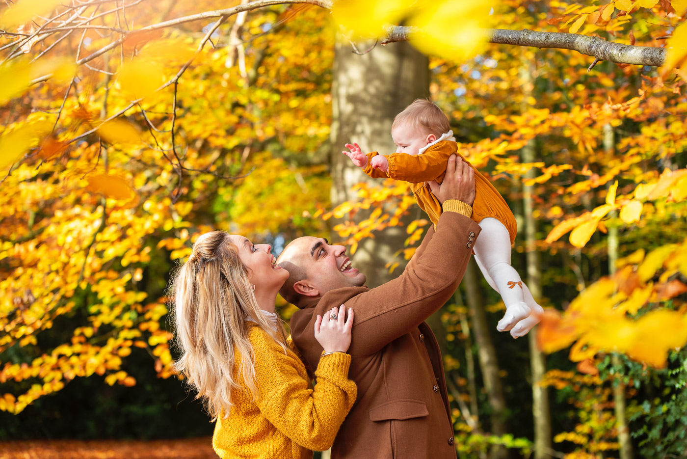 Autumn photo session with matching dressed family and a baby in colourful woods
