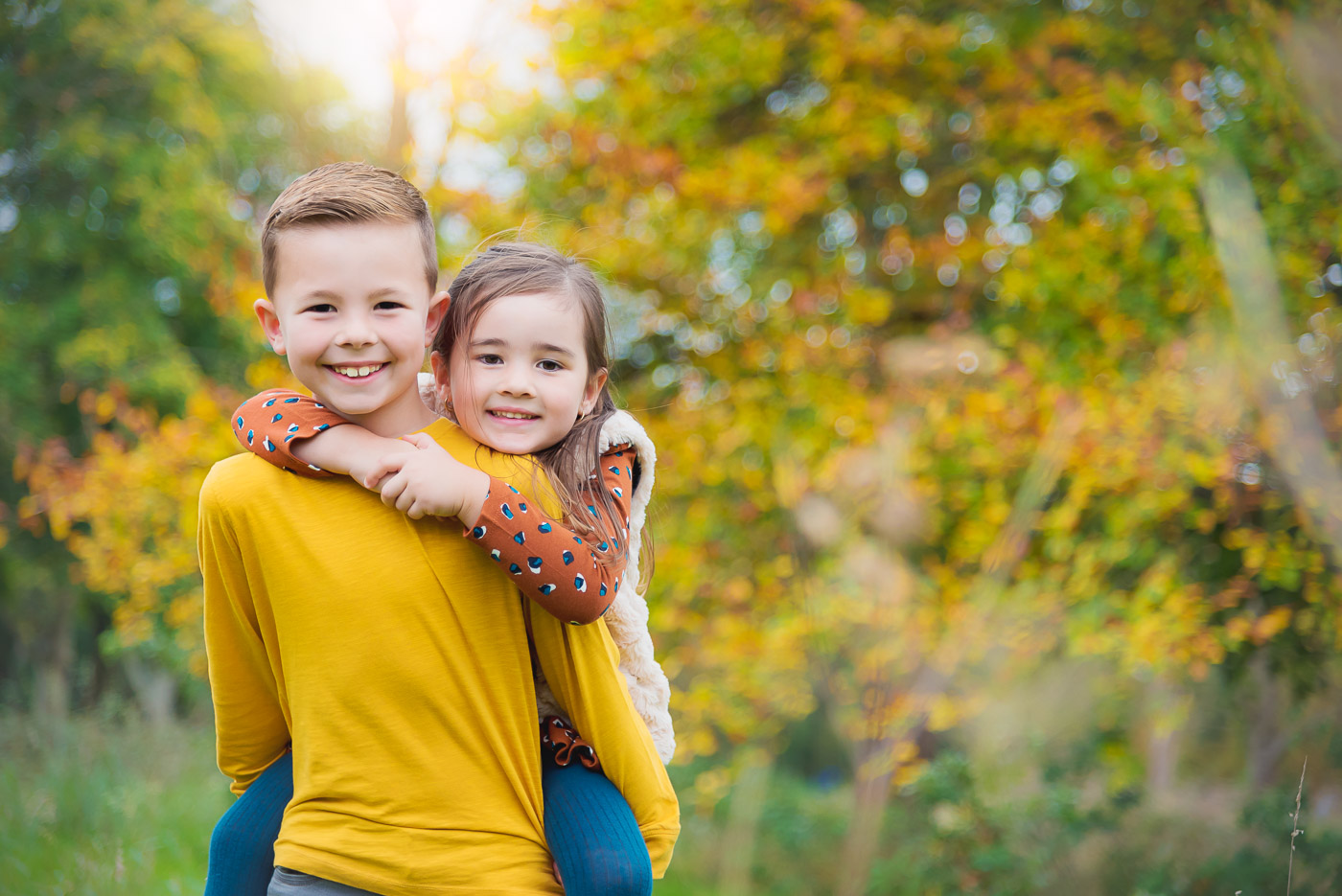 Brother with amazing smile carrying his younger sister on back through colourful autumn woods