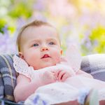 Lovely baby girl with stars in her eyes lying in a spring flower bucket among bluebells