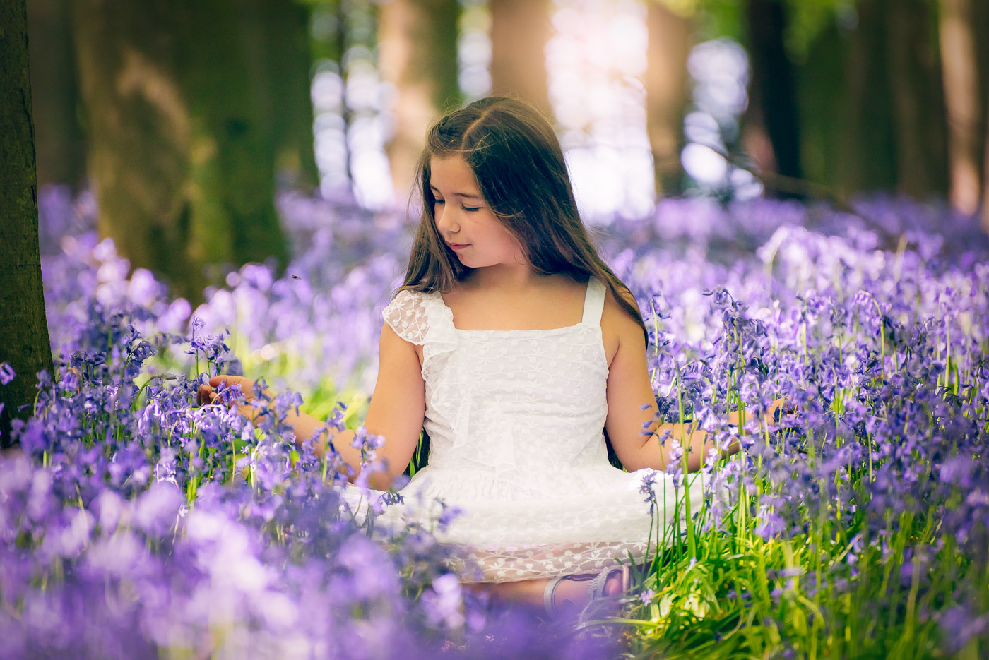 Young girl in a white dress sitting with bluebells and playing with their blossoms