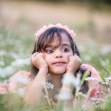 Lovely girl with hairband lying in the grass with flowers