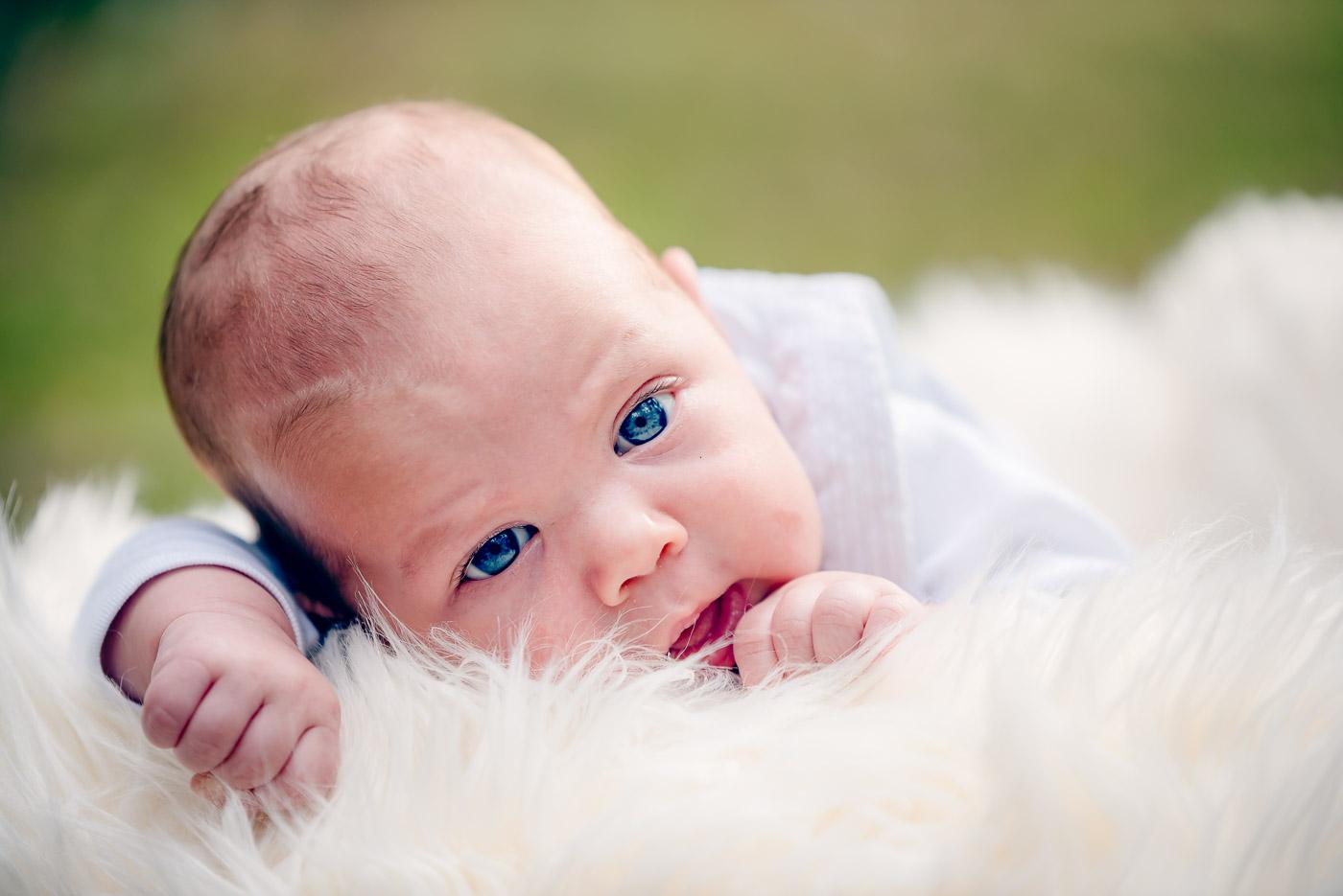 Newborn baby with amazing blue blue eyes lying on the fluffy white blanket