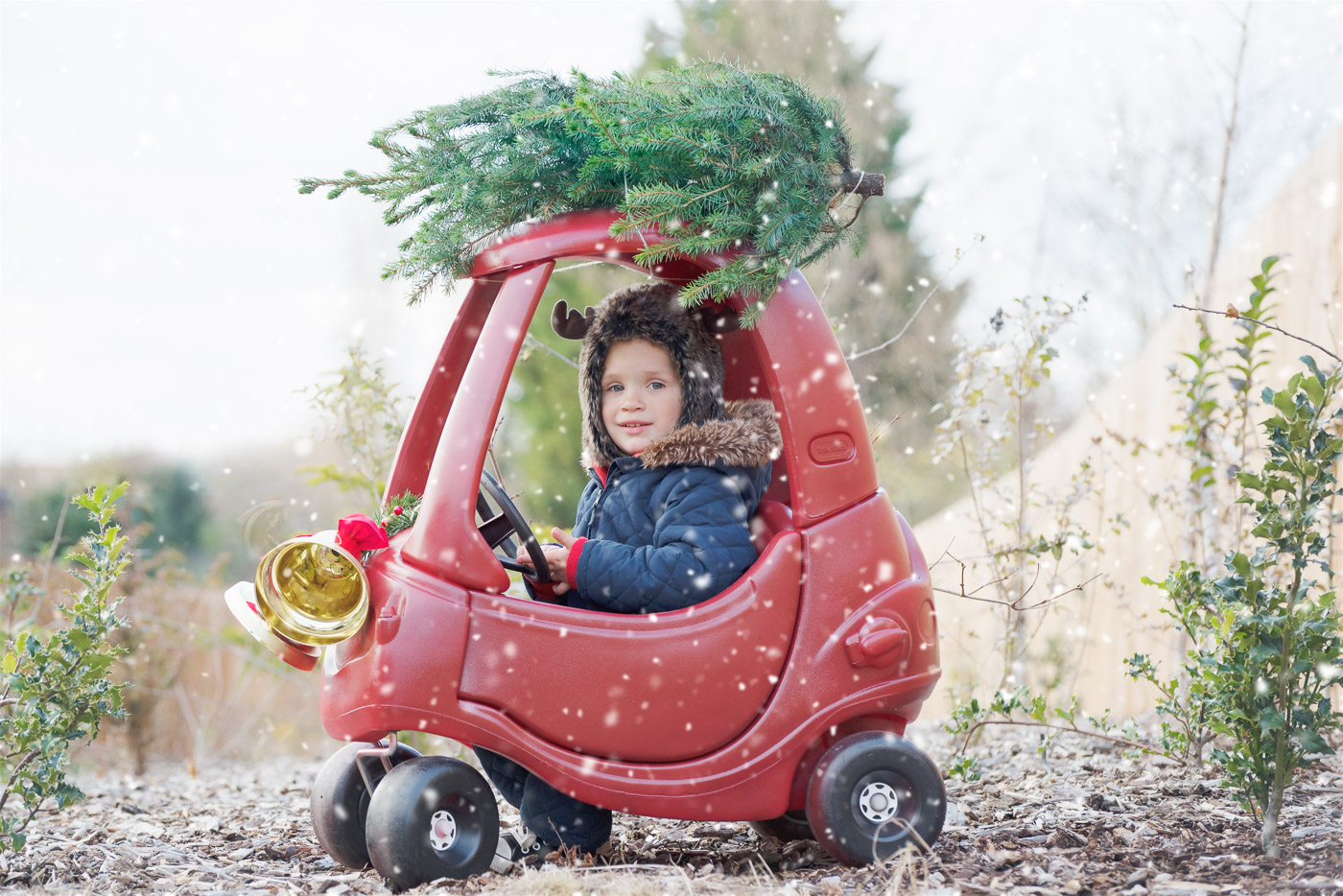 Little boy with reindeer hat driving a red little tikes car with Christmas tree on top