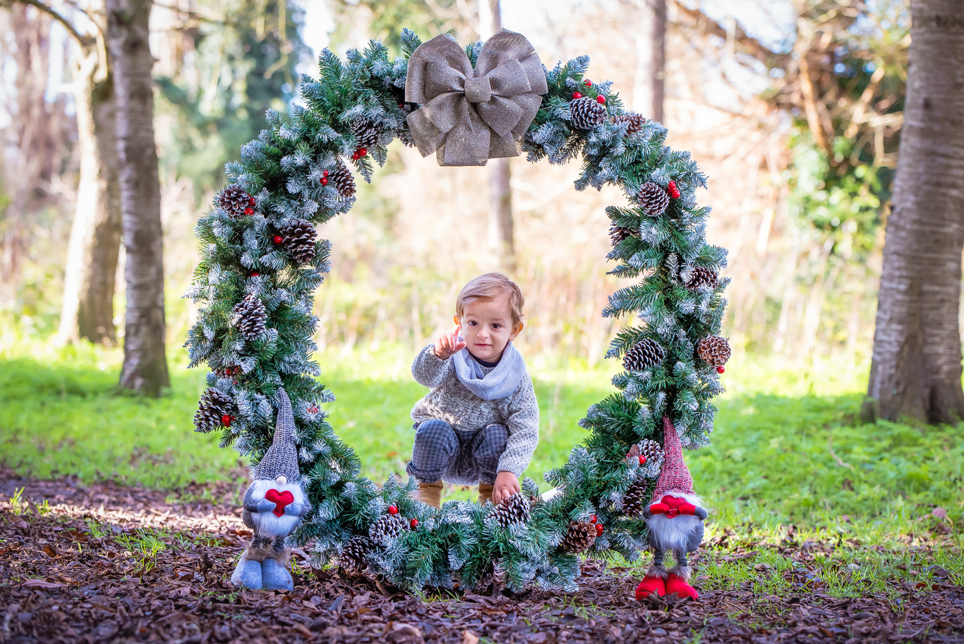 Little boy pointing with finger to mommy from the inside of a giant Christmas wreath