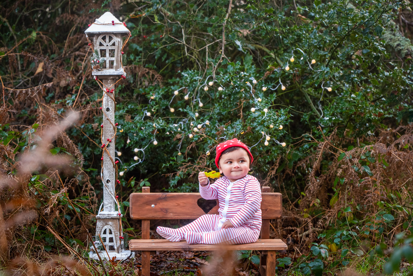 Christmas photography of a young girl in festive clothes, sitting on the rustic wooden bench next to magical scenery and lampost