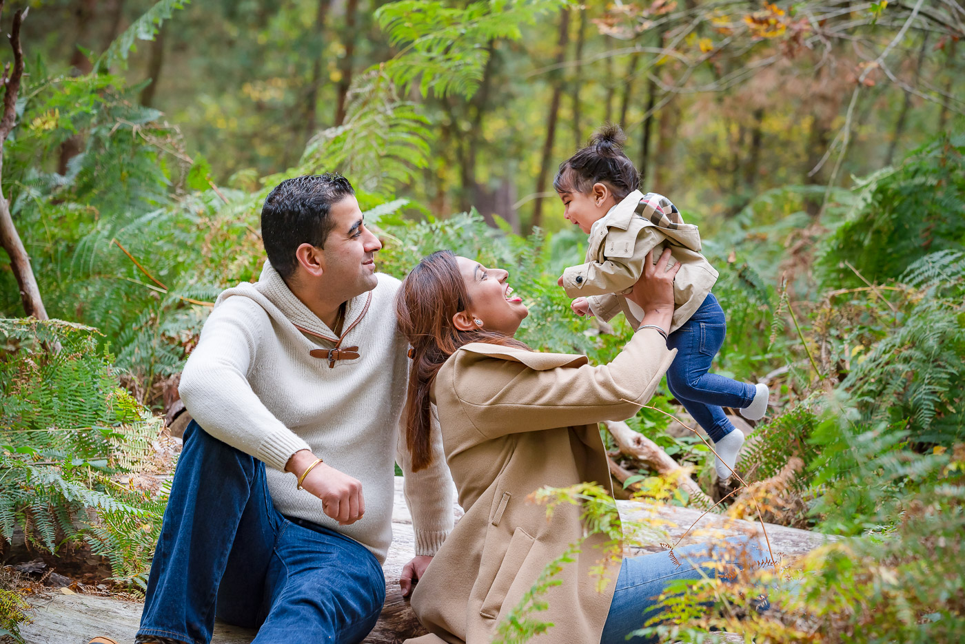 Outdoor photo session of a fun and relaxed family on logs in autumn woods