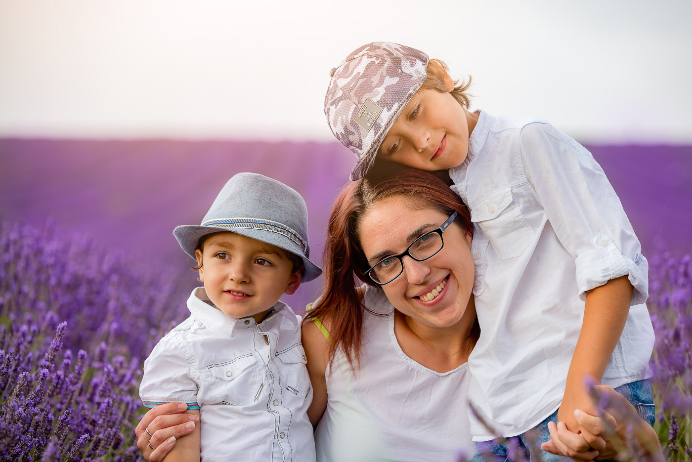 Lavender family photo of a proud mommy and her two sons with hats and matching dreses