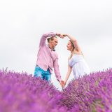 Lavender field photoshoot with a couple making heart with their hands