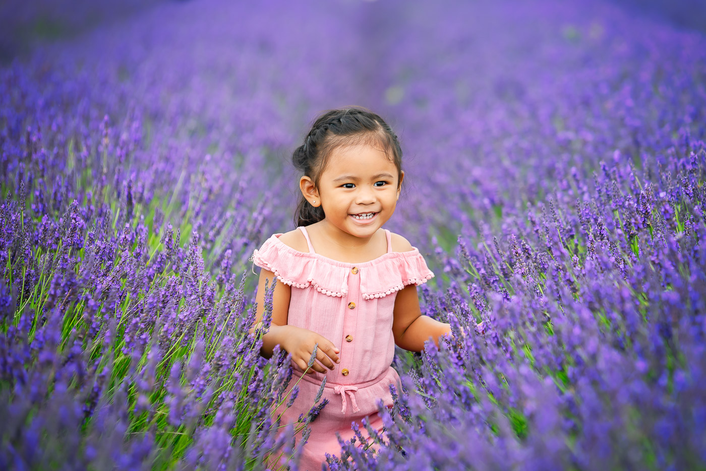 Young lovely girl running through purple field in beautiful pastel rose dress