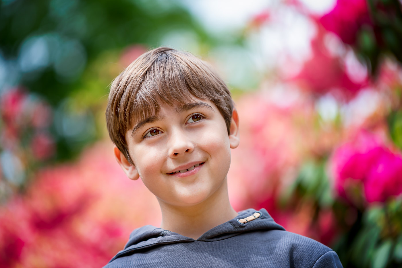 Close up portrait of a smiling tweenager boy in rhododendrons garden