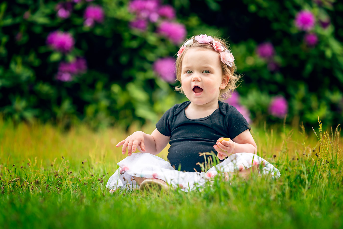 Gorgeous and adorable little girl sitting on grass with purple rhododendrons behind her