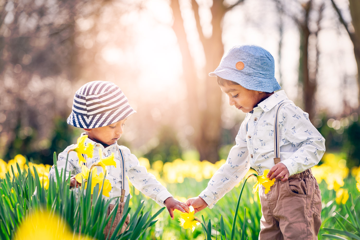 Spring family photoshoot with brothers holding hands and having matching dresses among spring flowers