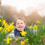Spring family photoshoot with a smiling boy among daffodils