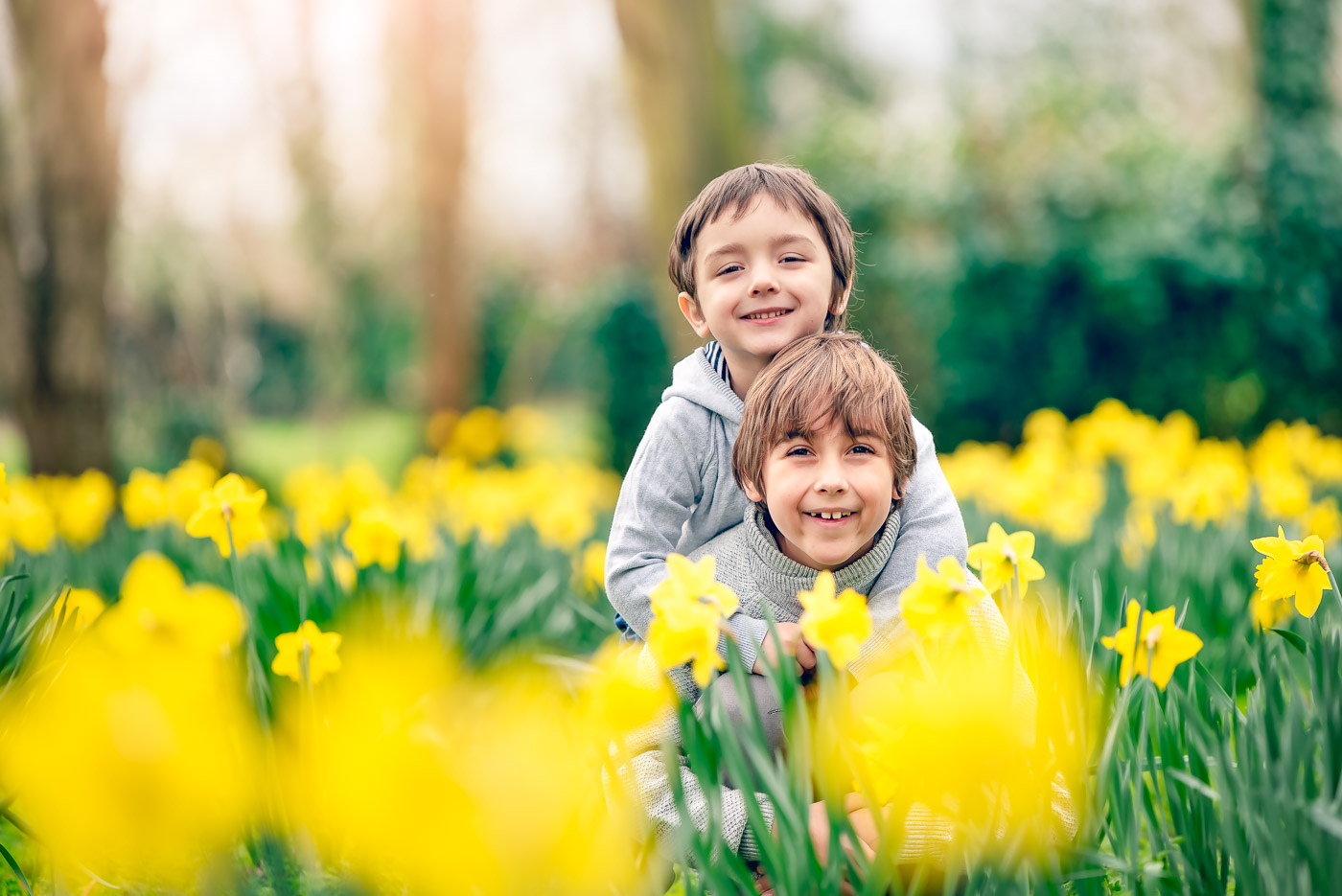 Two brothers in matching jumpers having fun on the daffodil field in park